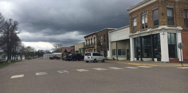Große Autos stehen in der Straße, keine Menschen sind zu sehen, dunkle Wolken