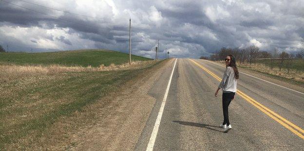 Die Autorin Paulina Unfried auf einer langen Straße im Nirgendwo